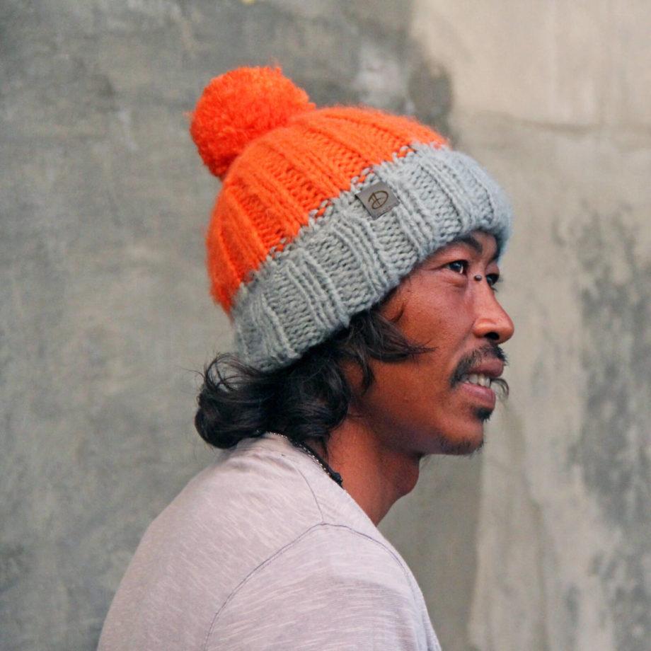 Man wearing LOTUS orange beanie